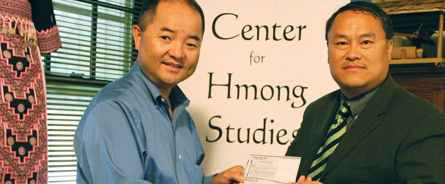 Dr. Jerry Yang, left, gives Lee Pao Xiong a donation for Concordia University's Center for Hmong Studies.